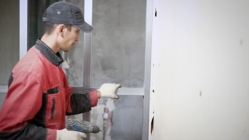 portrait of a man who finished installing an aluminum profile on the wall  during a renovation