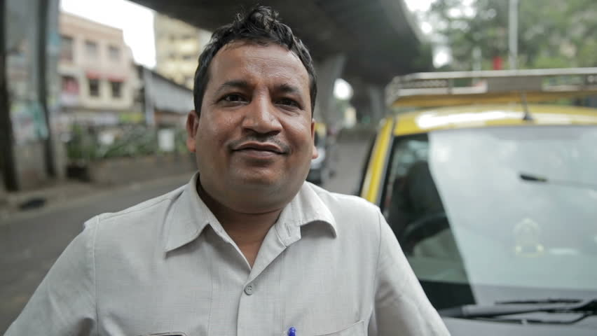 A close up and candid shot of a proud and smiling taxi driver standing in front of his taxi while vehicles passing in the background #33344998