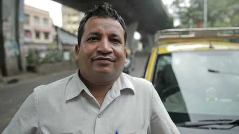 A close up and candid shot of a proud and smiling taxi driver standing in front of his taxi while vehicles passing in the background