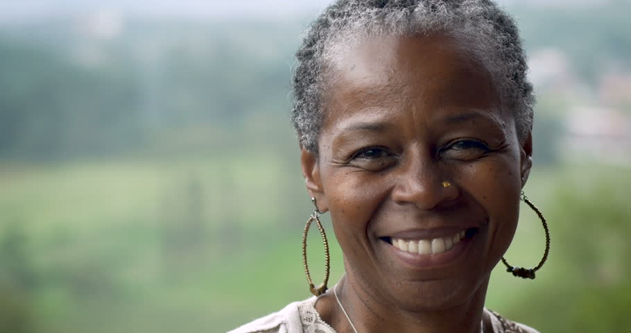 Portrait of a stunning African American woman in her 60s smiling at the camera outside #33363928