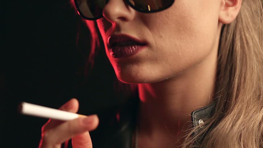 Portrait of elegant blonde woman in glasses smoking a cigarette on black background in studio | Shutterstock HD Video #33392488