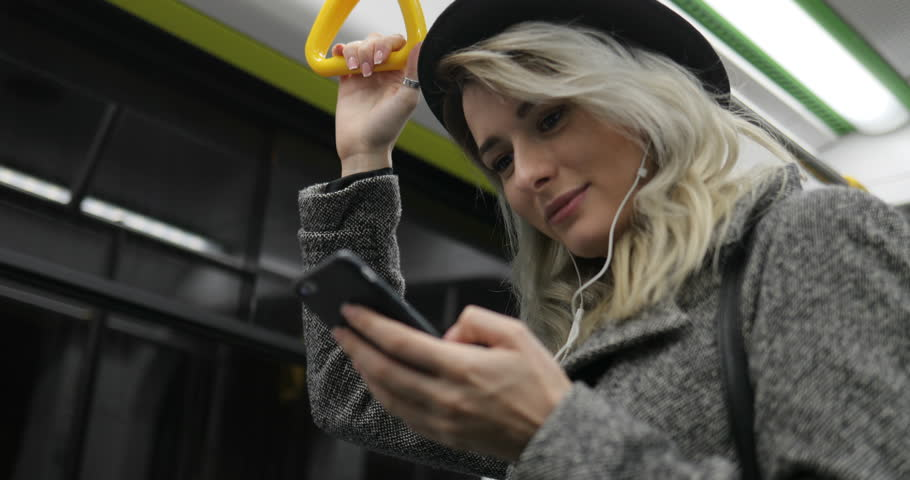 Portrait of cute girl in headphones holds the handrail, listening to music and browsing on mobile phone in public transport. City lights background #33427588