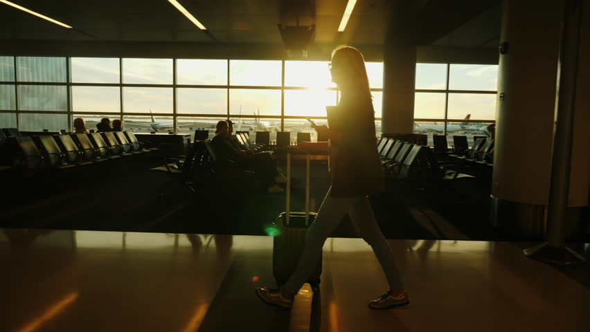 A business woman with a smartphone in her hand and a heap of luggage walks the terminal of the international airport.