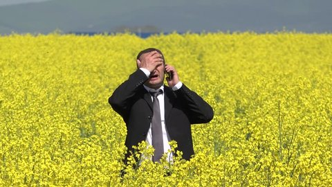 Businessman receive a phone call with bad news, man in blossom rape field