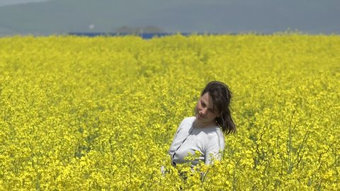 Beautiful woman enjoy to stand in yellow rape field, hair and plants dance in wind, feeling free, nature embrace