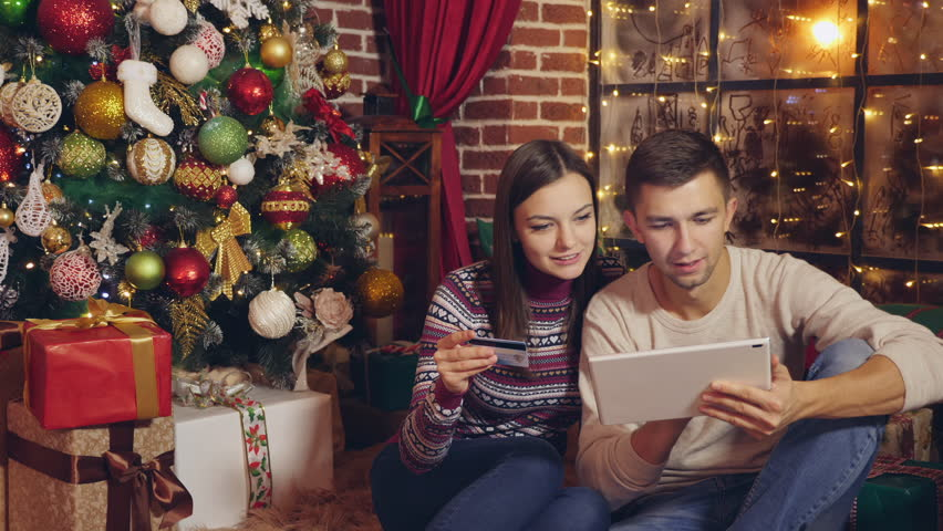 Online christmas shopping. Happy young couple using credit card to shop online. Happy Young man and woman with digital tablet and credit card buying online.