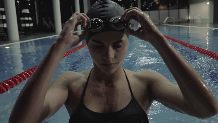 Sports woman floating breaststroke in blue water swimming pool. Close up woman in goggles training breaststroke style on blue water path in swimming pool 60 fps