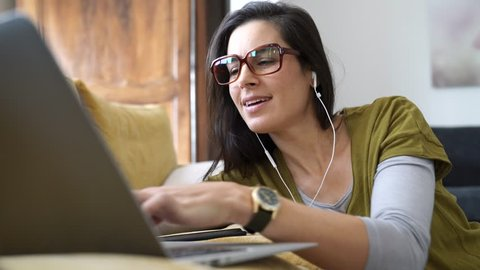 Trendy woman relaxing at home connected with laptop