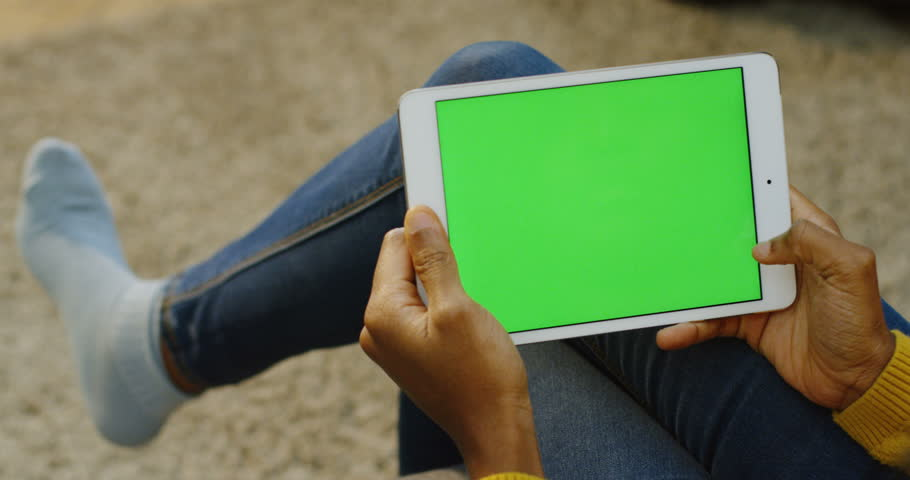 African american woman's hands scrolling and taping on the white horizontal tablet device while she sitting at home without shoes. Over shoulder. Green screen. Chroma key   Shutterstock HD Video #33502687