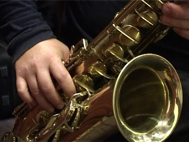 Musician is playing on saxophone. Close-up on fingers pressing the keys of the instrument.