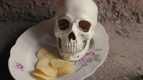 The concept of harmful junk food. Skull and falling chips. Slow motion.