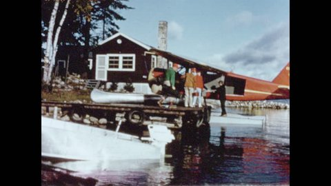 1950s: People line up, give luggage to man who loads luggage into bush floatplane parked on water. Man gives a boat motor to man who loads it into floatplane. Two men load a canoe into floatplane.
