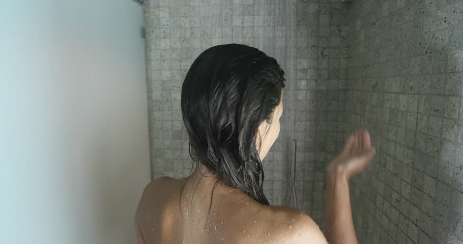 Woman in shower putting shampoo showering and washing hair in bathroom.