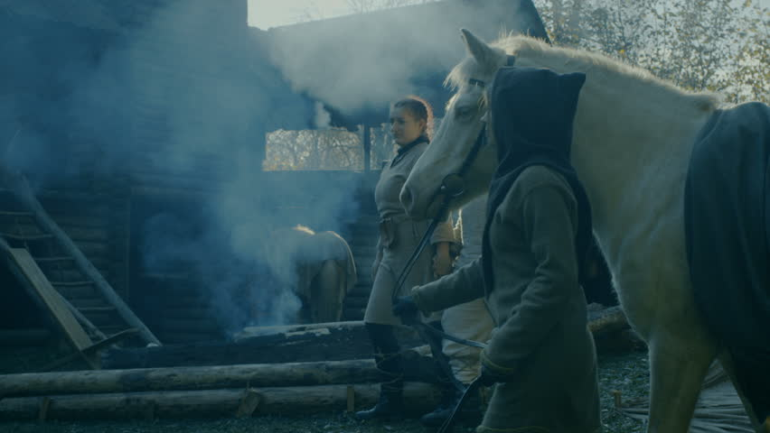 Medieval Reenactment. Life in the Yard of the Wooden Fortress, People with Horses. Shot on RED EPIC-W 8K Helium Cinema Camera.