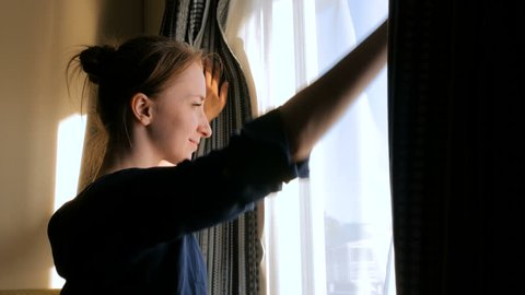 Happy woman opening curtains and looking out of window in cabin of cruise ship at morning