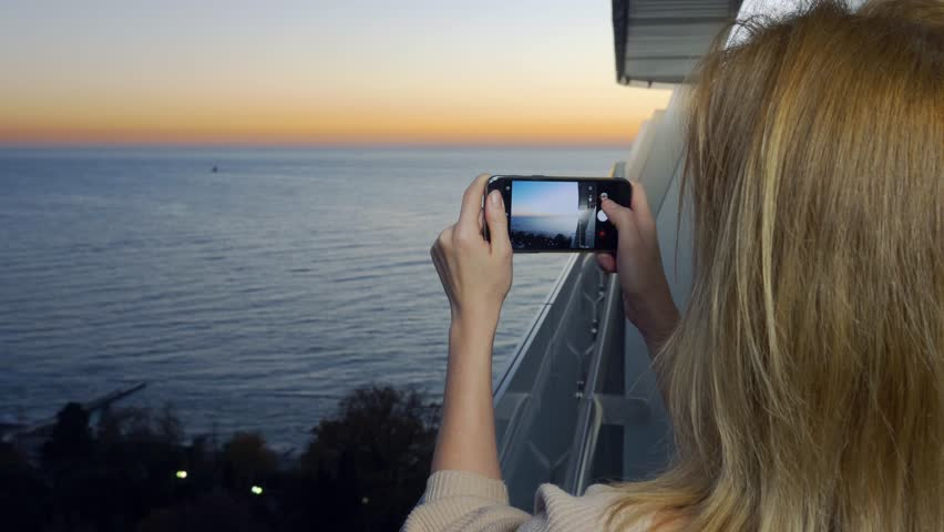 An attractive young woman using a smartphone at the balcony of a spa hotel, A woman is photographing a sunset by the sea using an application on a smart cell phone. 4k | Shutterstock HD Video #33586111