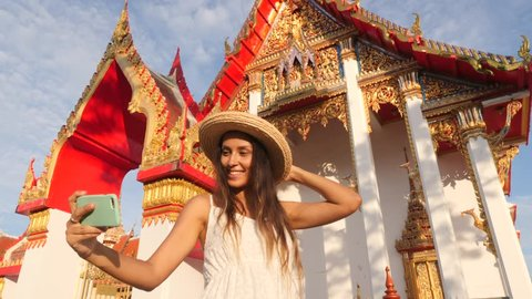 Attractive Young Mixed Race Tourist Girl in White Dress and Big Straw Hat Taking Selfie Photo with Mobile Phone at Thai Buddhist Temple. Phuket, Thailand. 4K, Slowmotion.