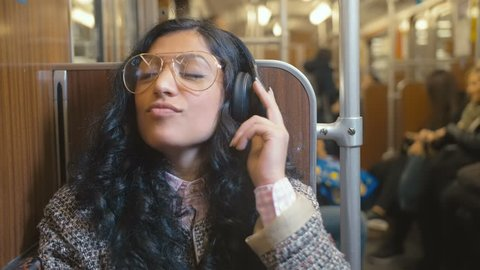 portrait of stylish and fashionable brunette rides in a train car and listens with music on headphones with pleasure Video slowed to 2 times the actual speed