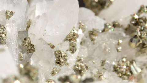 MACRO DOF: Glimmering opaque quartz with metallic pyrite creating a beautiful image. Translucent white semi precious quartz with golden pyrite particles shining like ice and sun under bright lights.