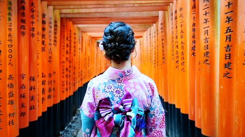 Asian women in traditional japanese kimonos walking at Fushimi Inari Shrine in Kyoto, Japan.