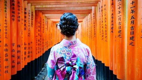 Asian women in traditional japanese kimonos walking at Fushimi Inari Shrine in Kyoto, Japan.