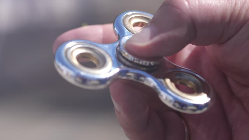 Close up of man playing with fidget spinner in slow motion. 1920x1080 | Shutterstock HD Video #33653788
