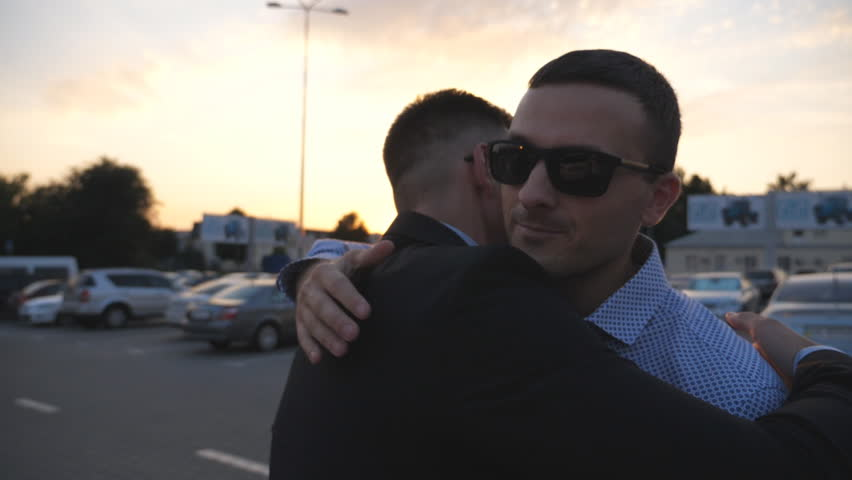 Two young businessmen farewell and hugging each other outdoor. Colleagues or business partners embrace and diverge in urban environment. Parting between good friends outdoor. Slow motion