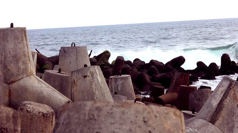 Sea wave crashing tetra concrete block or wave breaker stone at glagah beach. film look color grading with sea wave background sound