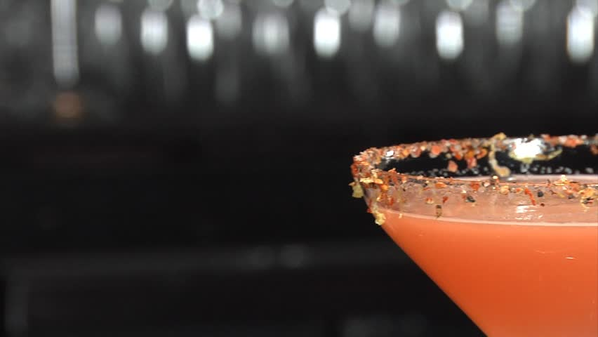 Sugar is sprinkled onto martini/ Pink Martini is flavored with sugar by a bartender
