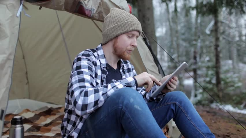 Man with a tablet in a tent on the shore of a winter lake | Shutterstock HD Video #33703708