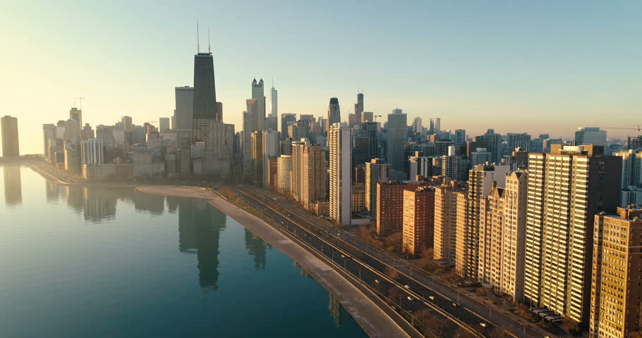 Flying above Chicago Downtown skyline at sunrise. Road by the shore with cars