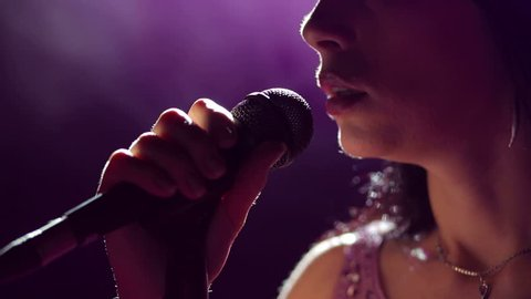 Close-up of the face of the singer with microphone on a black smoky background. The singer sings a song on stage in the dark, smoke, purple light, concert.