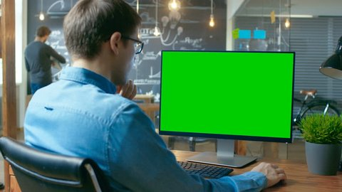 Young Man Works at His Desk on the Personal Computer with Mock-up Green Screen. In the Background His Colleague Works in the Creative Office.