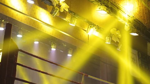 Empty boxing ring with yellow spotlight
