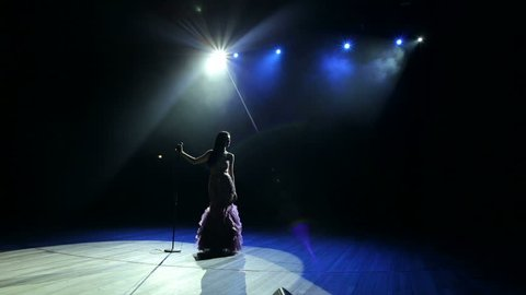 Luxurious singer stands on stage in a long dress in the dark and holding a microphone stand. Wide shot.