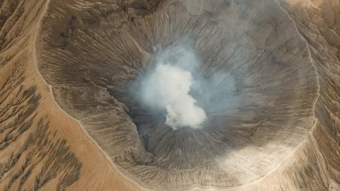 Crater with active volcano smoke in East Jawa, Indonesia. Aerial view of volcano crater Mount Gunung Bromo is an active volcano,Tengger Semeru National Park. 4K video. Aerial footage.