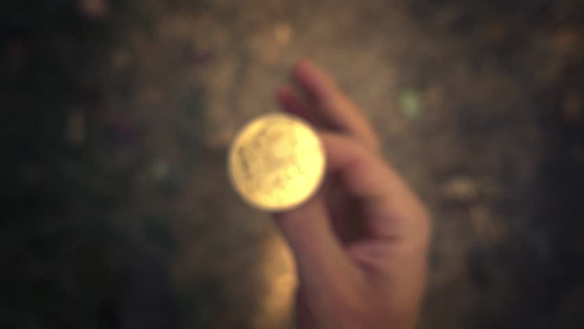 Hand flipping golden bitcoin coin and failing to catch it. Slow motion, closeup.