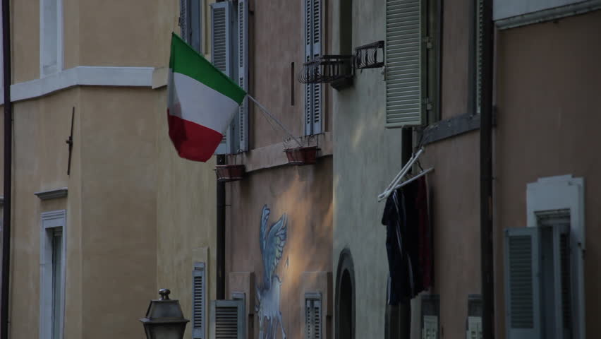 Walls and windows of a quiet Italian street. An Italian flag is prominently displayed from a windowsill.