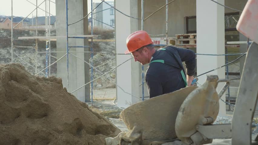 Caucasian worker pours sand into a concrete mixer with shovel at construction site, slow motion.