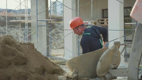 Caucasian worker pours sand into a concrete mixer with shovel at construction site, slow motion.