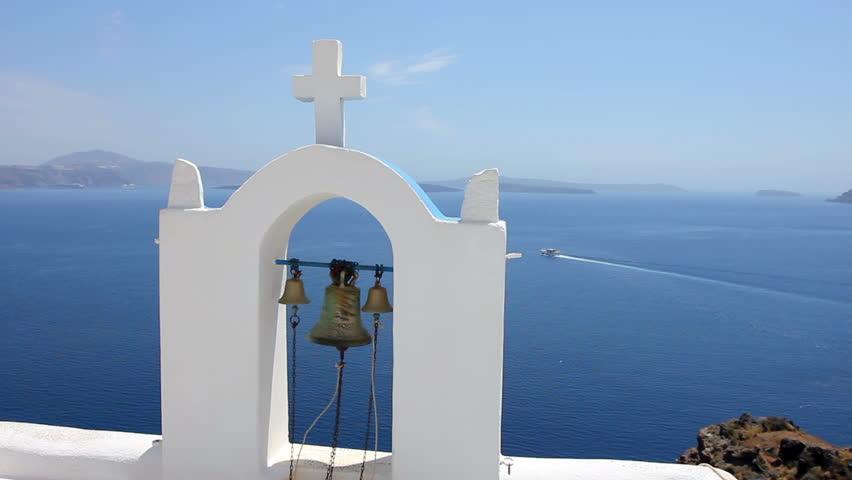 Calm sea, white church arch, cross, bells Island Santorini Greece.