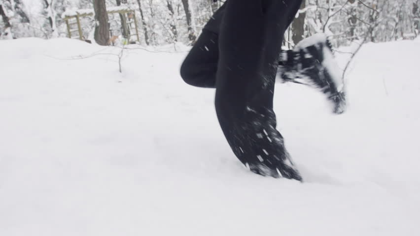 Slow Motion Of Young Sportsman Jogging Outdoors Through Snow