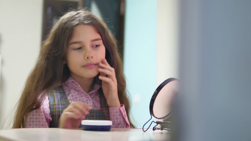 Little girl schoolgirl smears face cream. face care girl teenager is smeared with face cream indoors | Shutterstock HD Video #33878128