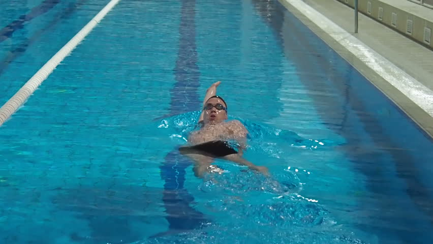 The athlete swims in the pool. A man is swimming with a backstroke in the pool. #33894178