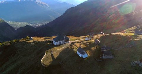 BEALP, VALLIS, SWITZERLAND -OCTOBER 15: Cinema 4k aerial tilt view over a hotel and a church, on a sunny fall evening, on bealp, in wallis, of the alps in Switzerland.mp4