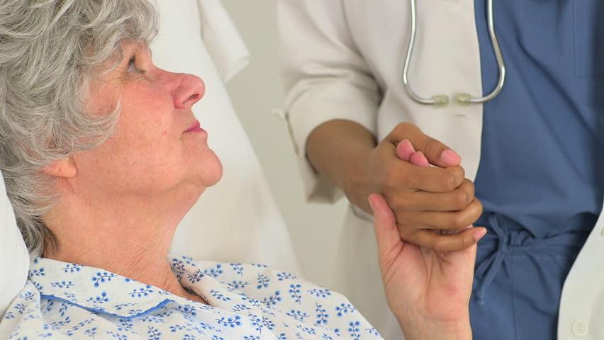Caucasian patient holding her doctor's hand