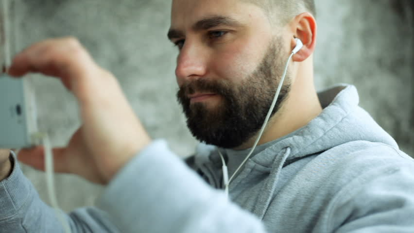 Art, people, emotions, music, 4K and lifestyle concept - Model released man in studio puts ear phones rocks, electronic out to music. Young handsome bearded man listens music smartphone in earphones | Shutterstock HD Video #33914908