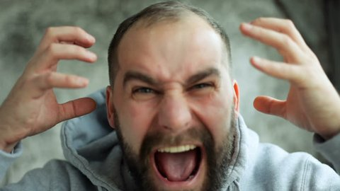anger, people, emotions, 4K and lifestyle concept - Model released man in studio screaming, smiling and winking at camera. Manifestation rage of man. Slow motion