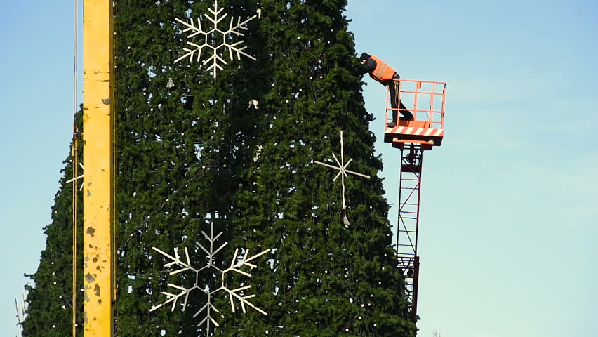 Decoration of a large urban Christmas tree. Workers on the crane install and decorate the Christmas tree.   Shutterstock HD Video #33918208