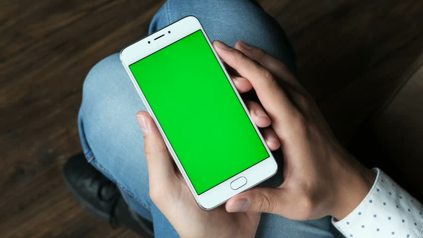 Guy hold cellular portable device with greenscreen chromakey closeup point of view. Human sitting, use handheld cellphone. Relax mood online by reading news, watch video, playing games and surfing | Shutterstock HD Video #33932548